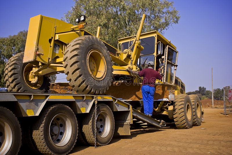 Caterpillar 140H Transporter. What a job an a half. Getting this huge Caterpillar 140H grader onto the back of it's long haul transporter partner royalty free stock photography