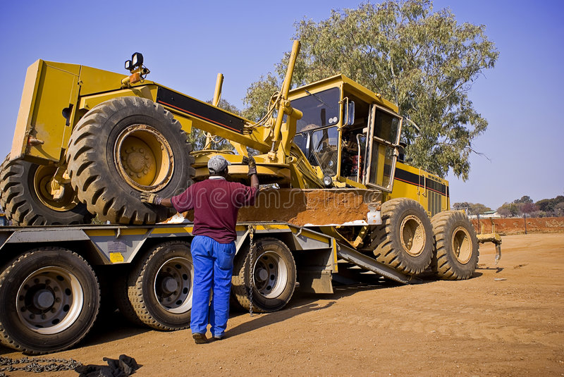Caterpillar 140H Transporter - On Flatbed Trailer. Heavy Duty Construction Equipment. Easy does it. Inching the large Caterpillar 140H grader into the correct royalty free stock photo