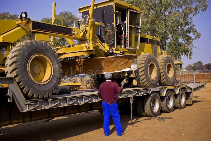 Caterpillar 140H Transporter - On Flatbed Trailer. Heavy Duty Construction Equipment. Easy does it. Inching the large Caterpillar 140H grader into the correct stock image