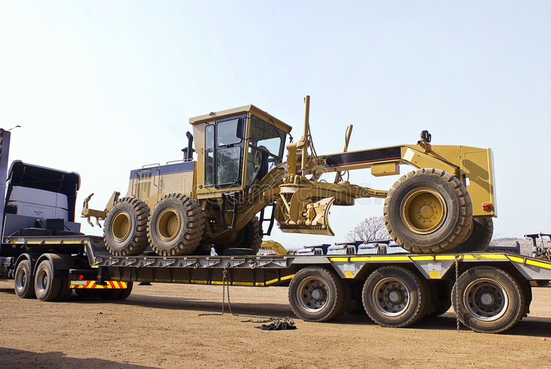 Caterpillar 140H Transporter - On Flatbed Trailer. Heavy Duty Construction Equipment. Transport arrived with the exchange unit. Before we can load the new one royalty free stock photos
