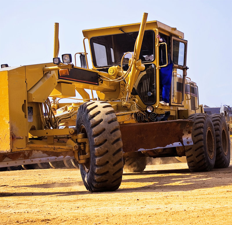 Caterpillar 140H - Turning. Heavy Duty Construction Equipment. Caterpillar 140H performing a full turn, during a parking exercise royalty free stock image