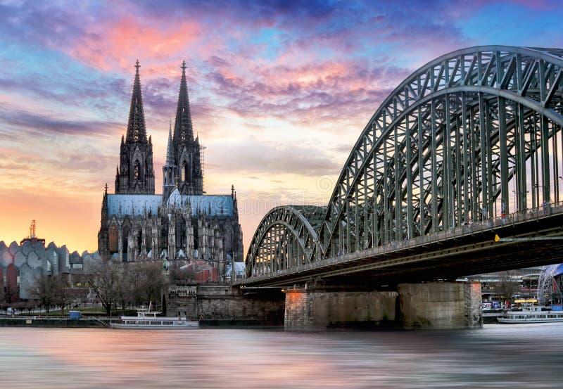 Cathédrale de Cologne et pont de Hohenzollern au coucher du soleil - nuit photo stock