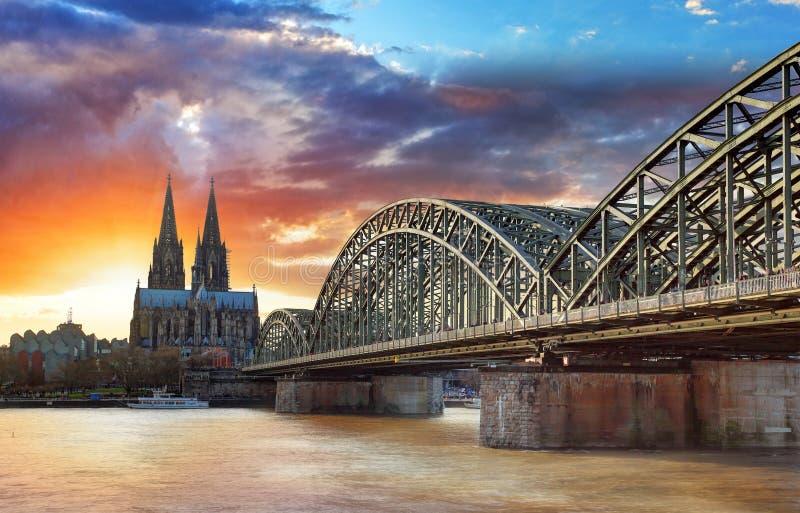 Cathédrale de Cologne et pont de Hohenzollern au coucher du soleil - nuit images stock