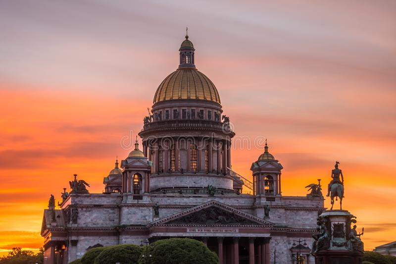 Cathédrale du ` s d'Isaac de saint dans la place, dans St Peterburg le soir sur un ciel orange lumineux de coucher du soleil photographie stock libre de droits