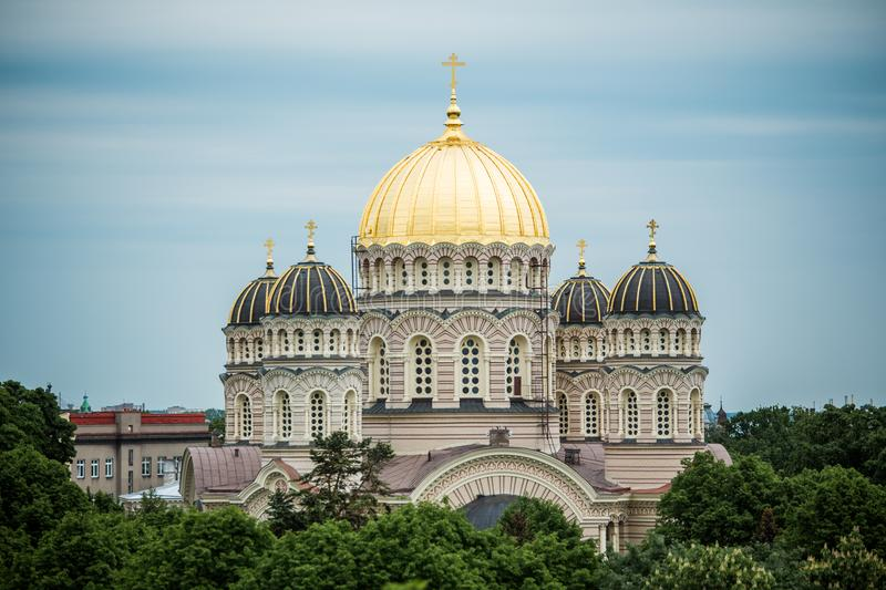 Cathédrale orthodoxe Golden Dome au-dessus des arbres de ville de Riga photo stock