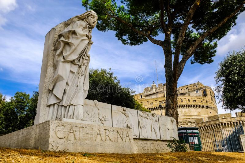 catharina Monumento alla st Caterina di Siena con il castello di Angelo del san nei precedenti fotografie stock