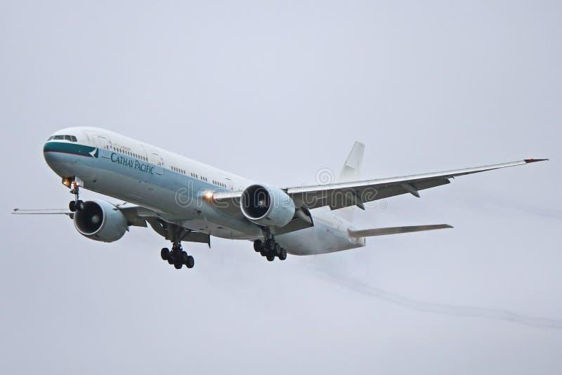 Cathay Pacific Boeing 777 eingehüllt in Contrails am Endstück lizenzfreie stockfotografie
