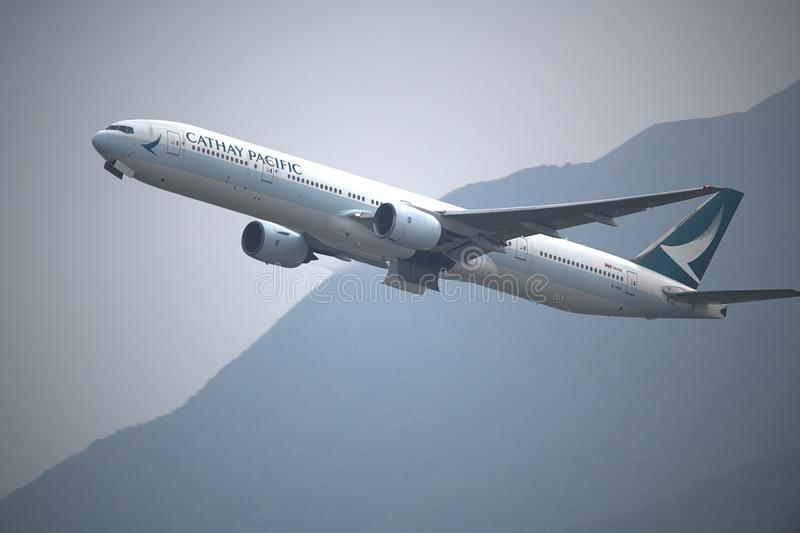 Cathay Pacific Boeing 777-367. 25th March 2018, 1744 hrs Cathay Pacific Boeing 777-367 taking off from Hong Kong Airport on a Cloudy day with the green hills of stock photography