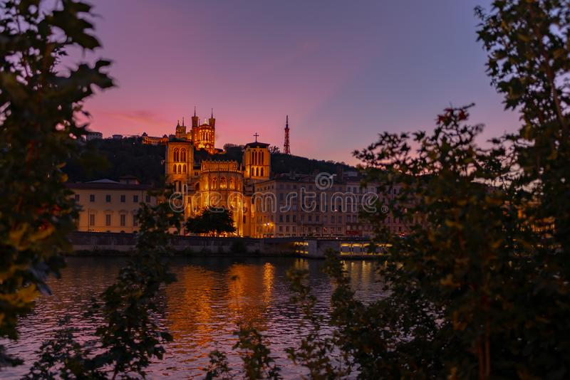 The cathedral and the basilica at dusk, Lyon, France. Foliage framing a view on the Lyon`s cathedral and the Fourviere`s basilica at dusk with pink sky and the royalty free stock image