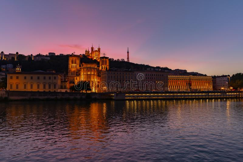 The cathedral and the basilica at dusk, Lyon, France. View on the Lyon`s cathedral and the Fourviere`s basilica at dusk with pink sky and the Saone river in stock images