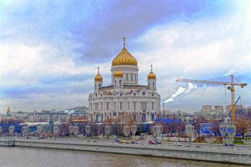 Cathedral of Christ the Savior. Moscow. Temple and golden domes on the background of the big city. Gloomy blue sky with clouds stock photos
