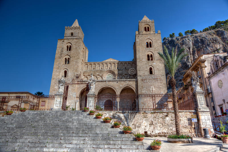 Cathedral - Duomo, Cefalu, Sicily, Italy. The Byzantine Cathedral or Duomo in Norman - Sicilian Romanesque style with staircase in front and rocks in the back royalty free stock photography