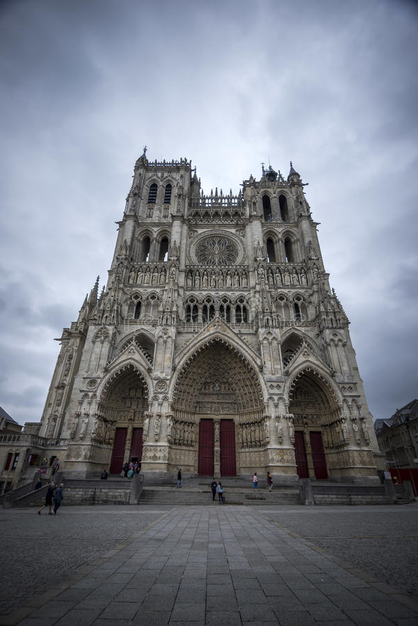 Cathedral and Gray Sky. The amazing Amience Cathedral with a gray sky background and people walking below, France stock images
