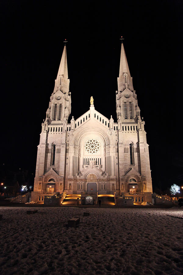 Cathedral illuminated at night. Exterior of grand cathedral building with tall spires illuminated at night with cobbled square in foreground royalty free stock image