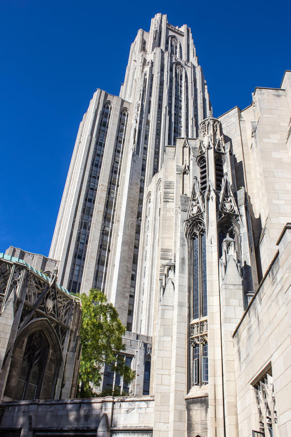 Cathedral of Learning Left. Cathedral of Learning Towers Over a Green Tree Against a Deep Blue Sky In Oakland a sub-city of Pittsburgh Pennsylvania stock image