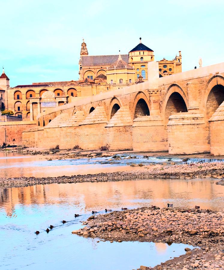 Mosque of Cordoba. Cathedral next to the mosque of Cordoba in the river Guadalquivir in a cloudy day royalty free stock images