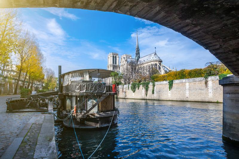 Cathedral of Notre Dame de Paris sunny autumn afternoon. Embankment of the Seine River. The natives and tourists take a walk and. Relax in warm weather. Blurred stock image