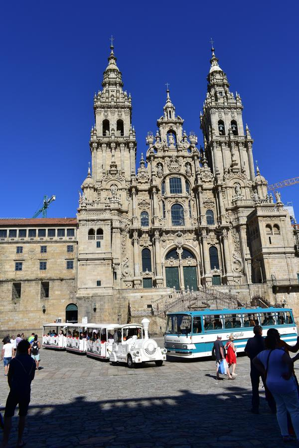 Cathedral with old bus, tourist train and pilgrims. Santiago de Compostela, Spain. stock images