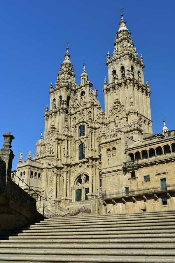 Cathedral: Side view from stairs. Baroque facade, Obradoiro, clean stone, blue sky. Santiago de Compostela, Spain. Cathedral, Santiago de Compostela. Spain royalty free stock photography