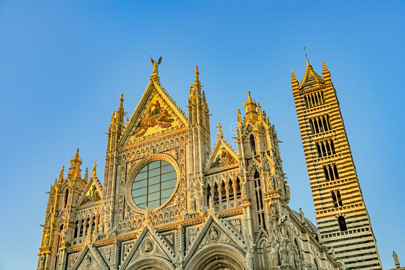 Cathedral in Siena Italy Tuscany, with White and Blue And Gray Striped Marble Round Window, Bell Tower, and Dome stock image