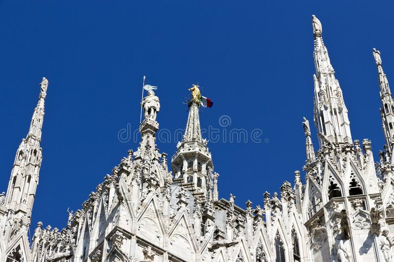 Milan Duomo Cathedral, gothic spires and golden statue of Madonna with italian flag. Blue sky background, top landmark stock images