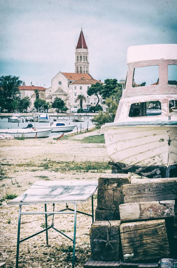 Cathedral of St. Lawrence, harbor and broken ship in Trogir, Croatia. Travel destination. Summer vacation. Analog photo filter with scratches stock images