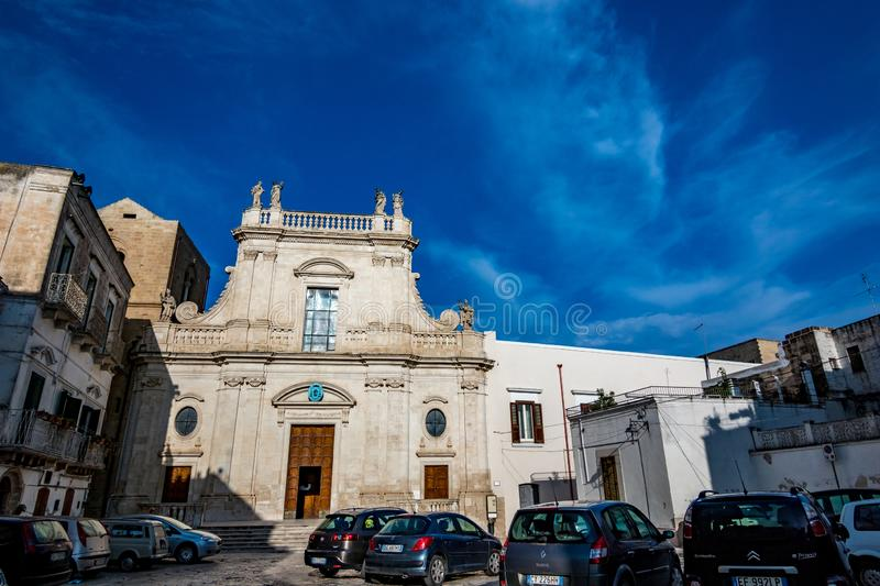 Cathedral of St. Nicola. Castellaneta.Puglia.Italy. CASTELLANETA, ITALY - AUGUST 27, 2018 - Public square is empty and only cars parked in front of Cathedral of royalty free stock images