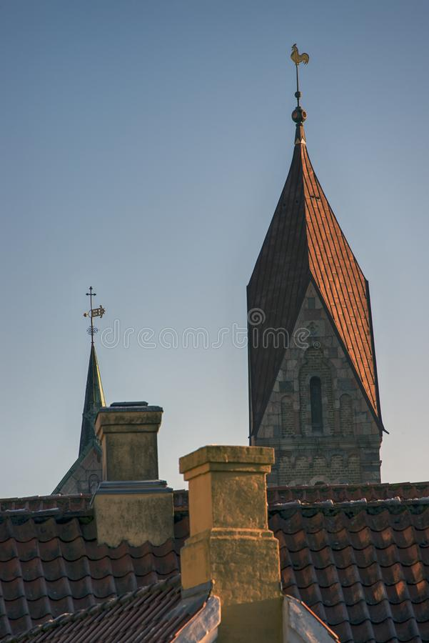 Cathedral tower, spire and chimneys. Cathedral tower and spire close to roofs and chimneys in Ribe, Denmark stock photos