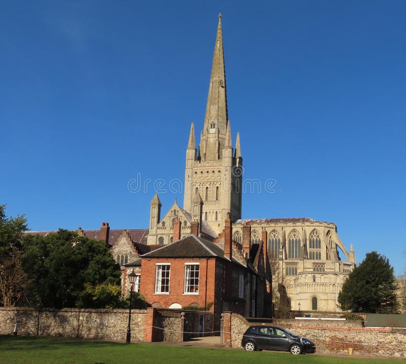 Norwich Cathedral on a spring day. He cathedral was begun in 1096 and constructed out of flint and mortar and faced with a cream-coloured Caen limestone. A Saxon royalty free stock images