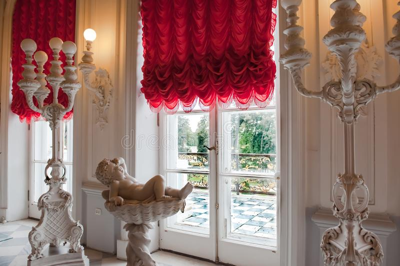 Catherine Palace, awaking Cherub laying in bowl in front of window with view to park of Catherine Palace, St. Petersburg, Russia royalty free stock photography