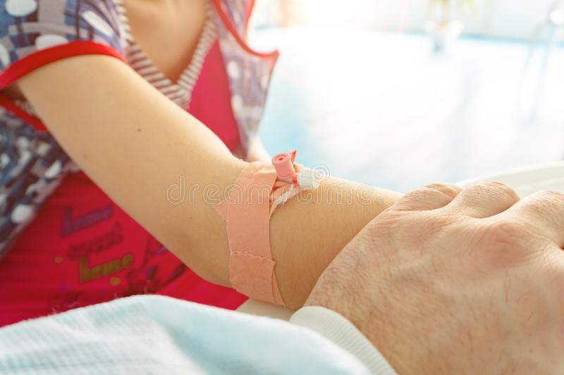 The catheter is in the girl's hand, and the doctor examines the patient stock photo