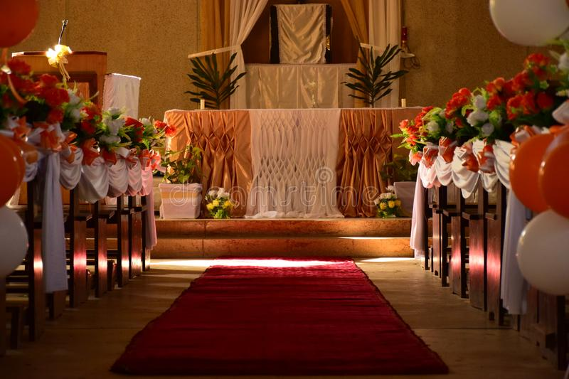 Church decoration on wedding day with flowers and ballons and a red carpet in orange theme and the sunrays falling through. This is a Catholic church in Africa royalty free stock image