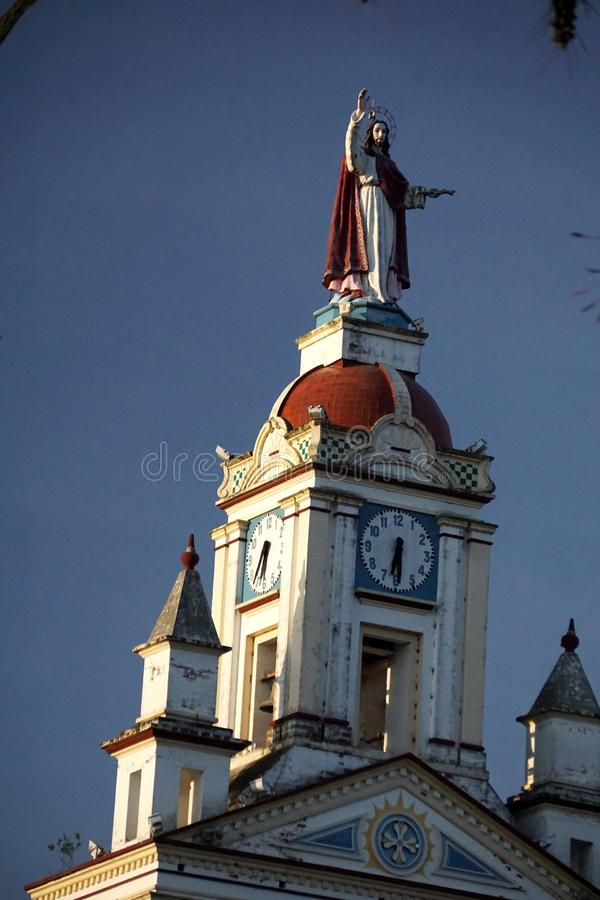 Catholic church in Cotacachi. Catholic church with red domes and a statue of Jesus on the clock tower on the square in Cotacachi, Ecuador royalty free stock photo