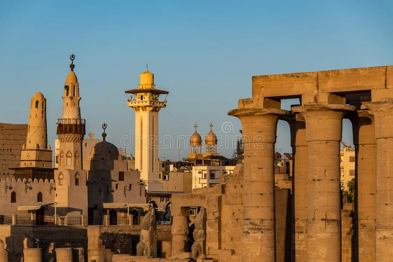 Catholic Church and Muslim Mosque Tower religion Symbols together in Luxor temple at sunset.  royalty free stock photography