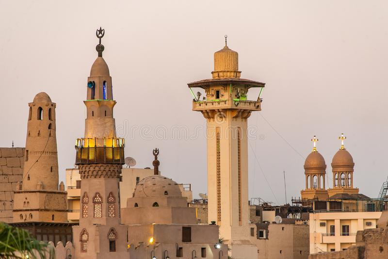 Catholic Church and Muslim Mosque Tower religion Symbols together in Luxor temple at sunset.  stock photos