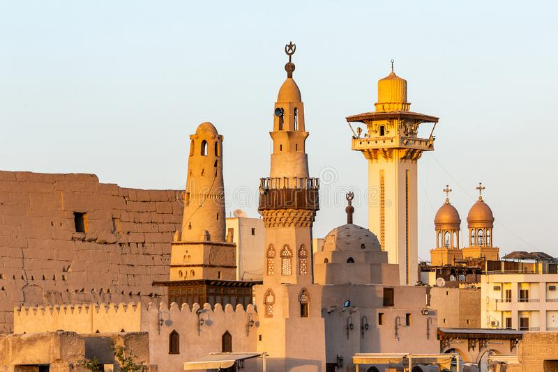 Catholic Church and Muslim Mosque Tower religion Symbols together in Luxor temple at sunset.  stock photo