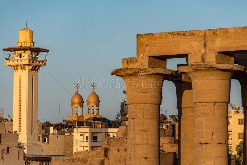 Catholic Church and Muslim Mosque Tower religion Symbols together in Luxor temple at sunset.  royalty free stock image