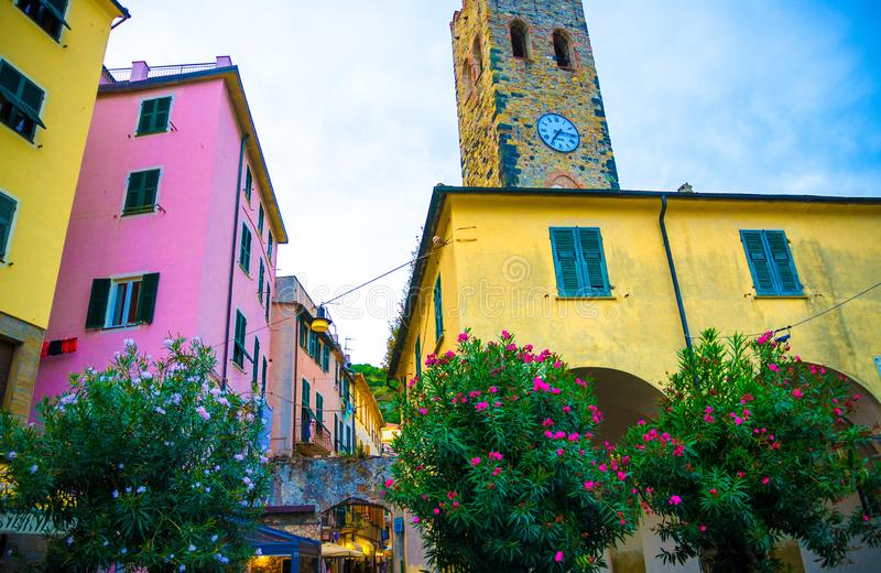 Catholic Church of San Giovanni Battista chiesa with clock tower, colorful buildings houses and flowers around in Monterosso villa. Ge, National park Cinque royalty free stock images