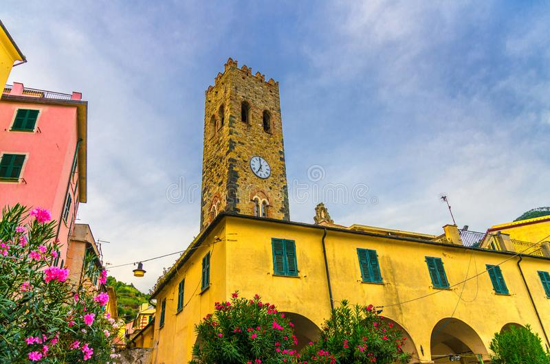Catholic Church of San Giovanni Battista chiesa with clock tower, colorful buildings houses and flowers around in Monterosso villa. Ge, National park Cinque stock photos