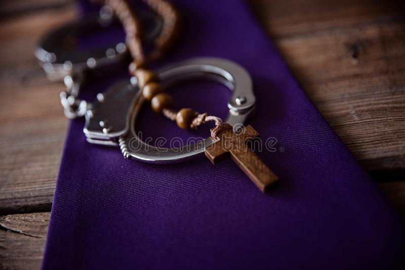 Catholic church symbols and handcuffs. Church and crime royalty free stock photos