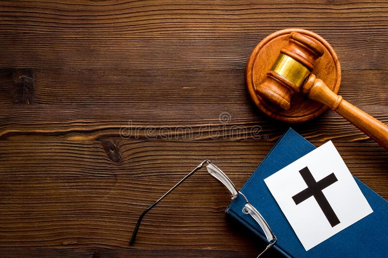 Catholic cross - catholicism religion concept - near gavel and book on wooden desk top view. Religious conflict concept.  stock photo
