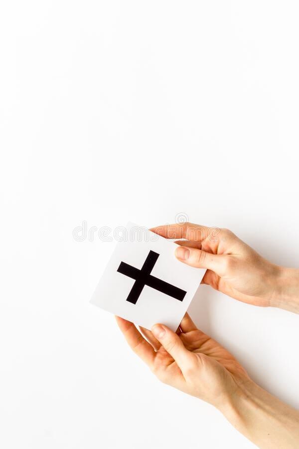 Catholic cross sign in hands - catholicism religion concept - on white background top view copy space. Catholic cross sign in hands - catholicism religion royalty free stock photography