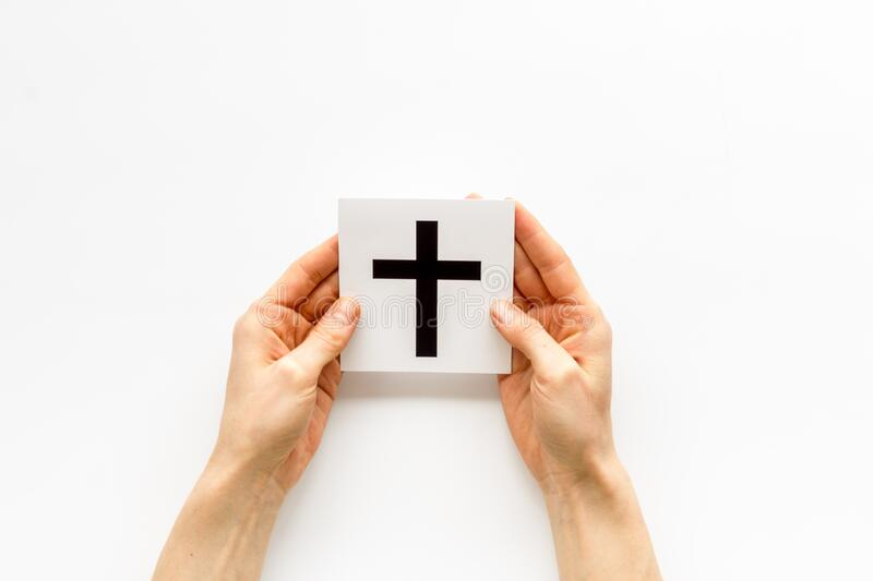 Catholic cross sign in hands - catholicism religion concept - on white background top view.  stock photos