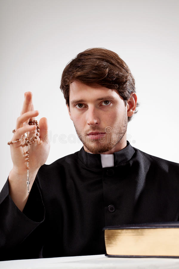 Catholic man with rosary in hand. And the Bible stock photos