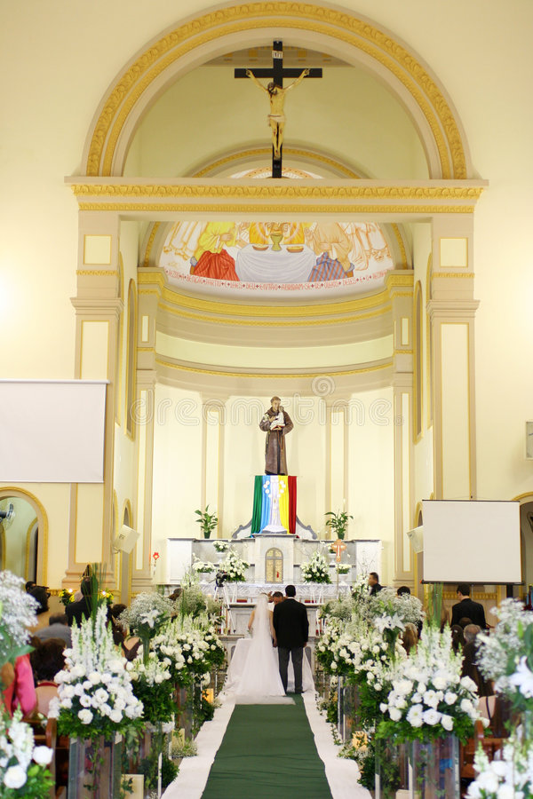 Catholic marriage. Church decorated with flowers and green carpet, ceremony of marriage royalty free stock photo