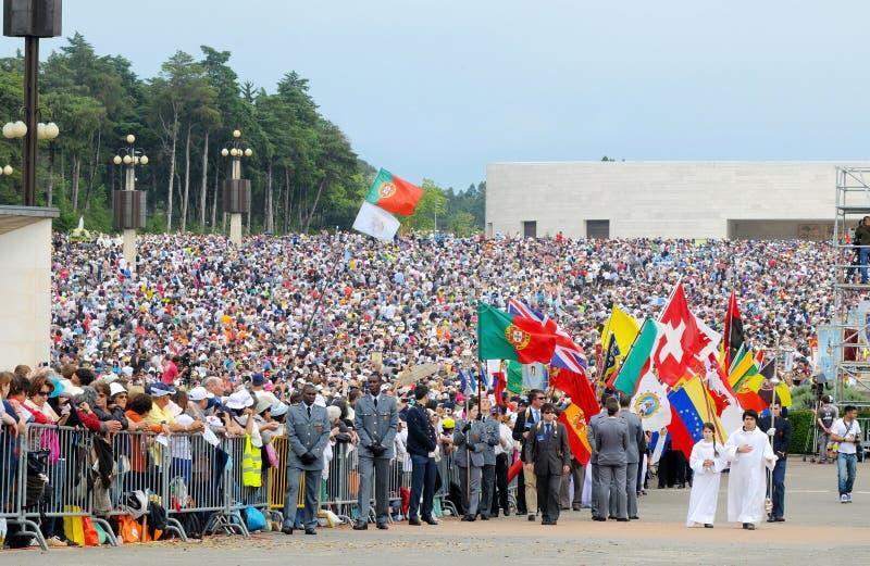 Catholic Pilgrims , Pilgrimage , Religion , Faith, Flags. Catholic pilgrims and devotees crowd with flags from Portuga, UK, Suisse, Spain, Venezuela among others stock photo