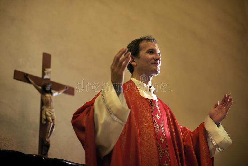 Catholic priest on altar praying during mass stock images