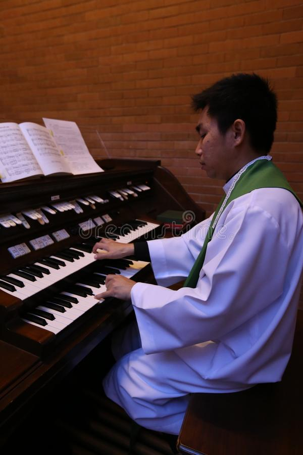 A Catholic priest playing the organ. royalty free stock photo