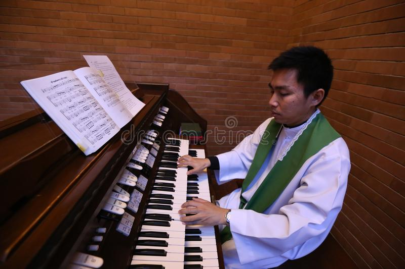 A Catholic priest playing the organ. stock images