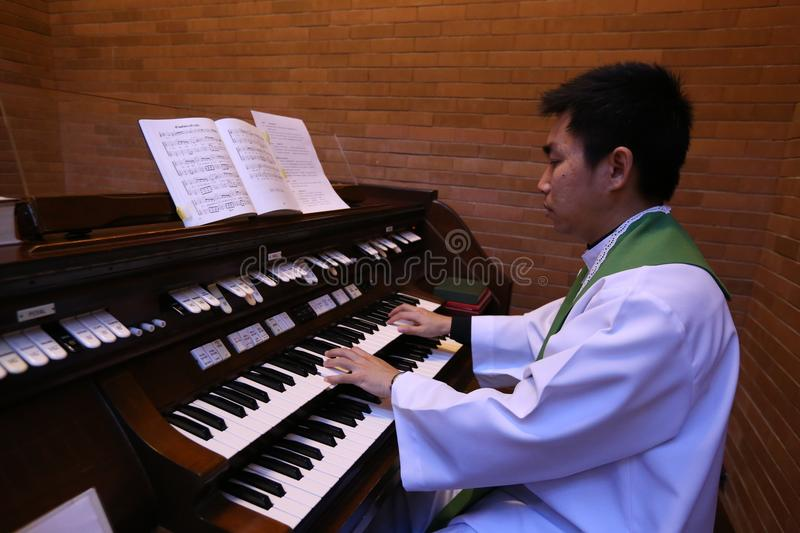 A Catholic priest playing the organ in the church. royalty free stock photos